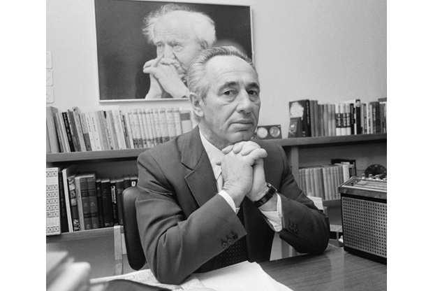 Shimon Peres in the 1970s, with a portrait of his mentor, David Ben-Gurion, on the wall behind him
