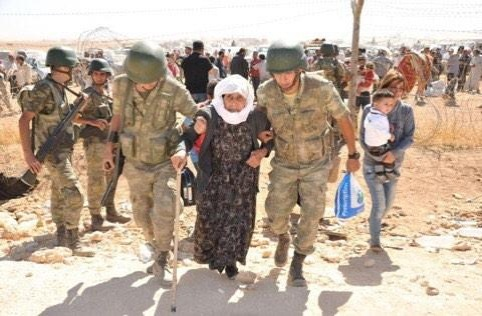 Turkish soldiers help a Syrian refugee