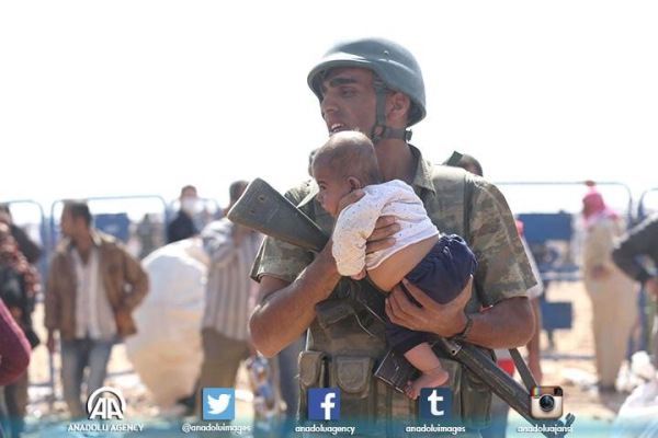 A Turkish soldier holds a Syrian infant