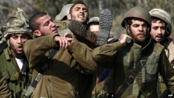 Israeli soldiers help a wounded buddy (BBC) after an incident on the Golan Heights