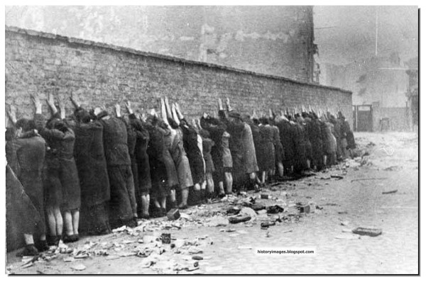 Jews in the Warsaw ghetto lined up to be shot by the Nazis